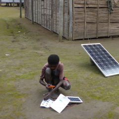 Local village boy charges household phone with solar charger